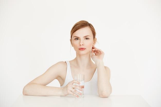 Giovane bella ragazza con pelle fresca pulita che giudica di vetro con acqua che si siede al tavolo. stile di vita di salute e bellezza.