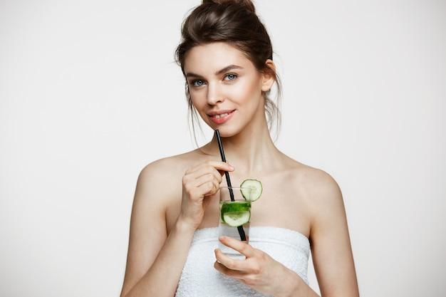 Giovane bella ragazza con pelle pulita perfetta che sorride esaminando macchina fotografica che tiene bicchiere d'acqua con le fette del cetriolo sopra fondo bianco. nutrizione sana.