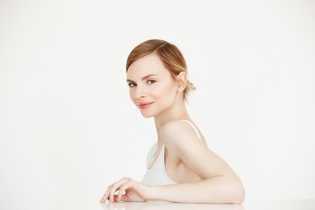 Giovane bella ragazza con seduta sorridente perfetta pelle pulita al tavolo. beauty spa e cosmetologia.