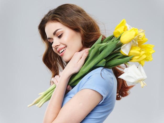 Giovane bella ragazza della primavera con i fiori, donna che posa con un mazzo dei fiori, festa della donna