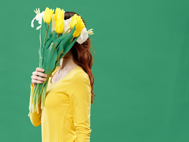 Giovane bella ragazza della primavera con la donna dei fiori che posa con un mazzo dei fiori, il giorno delle donne