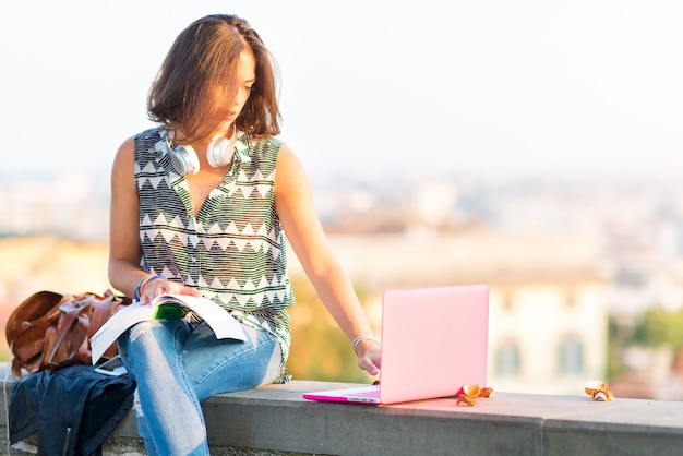 Giovane bella ragazza dello studente che studia con i libri e il computer sopra