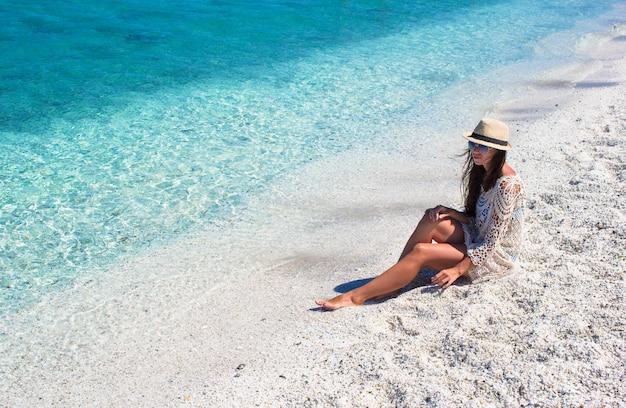 Giovane bella ragazza durante la vacanza italiana sulla spiaggia bianca