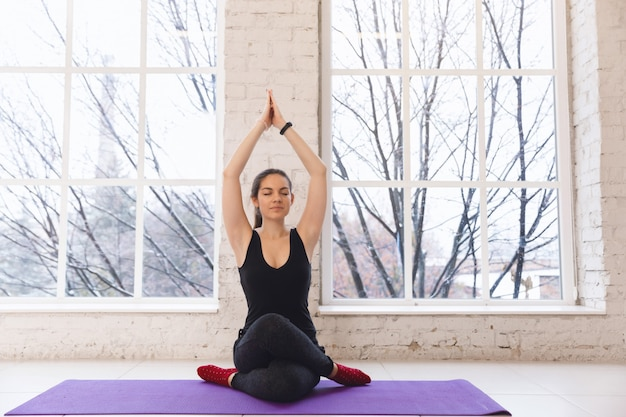 Giovane bella ragazza facendo yoga asana gomukhasana. mani in alto, vista frontale