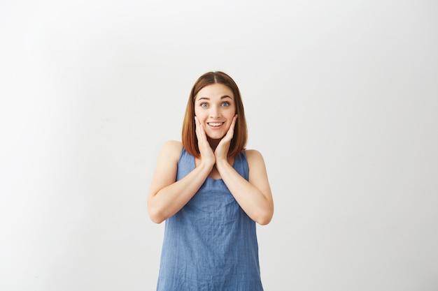 Giovane bella ragazza felice sorpresa che sorride con le mani sulle guance.