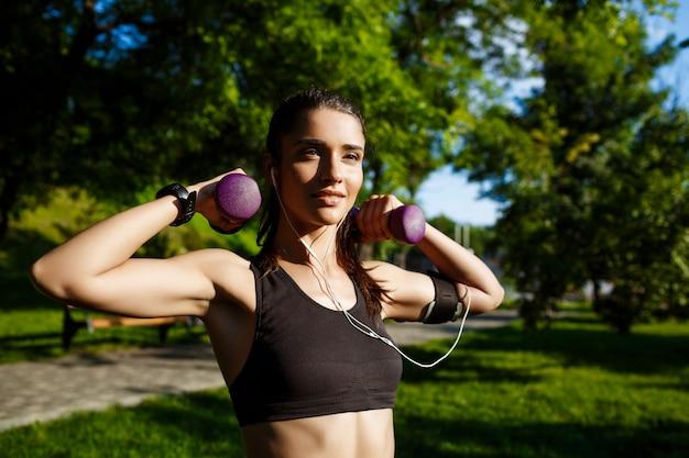 Giovane bella ragazza fitness tenendo manubri in natura