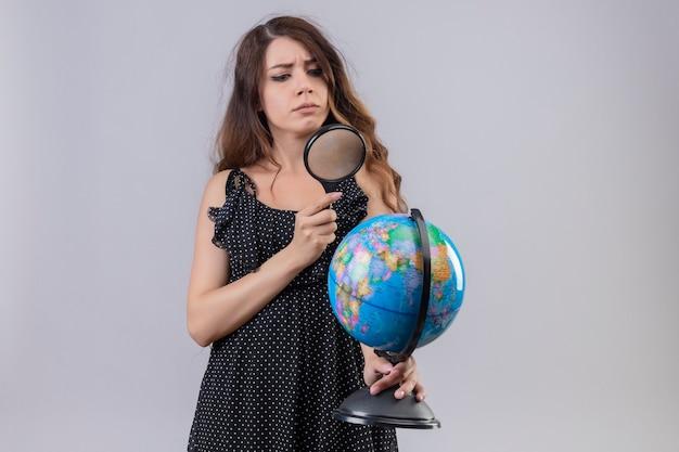 Giovane bella ragazza in abito a pois guardando il globo attraverso la lente di ingrandimento con la faccia seria in piedi su sfondo bianco