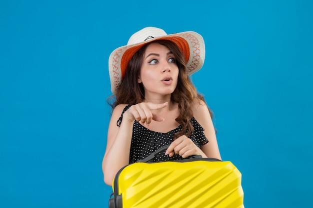 Giovane bella ragazza in abito a pois in cappello estivo che tiene la valigia che punta con il dito di lato guardando sorpreso in piedi su sfondo blu