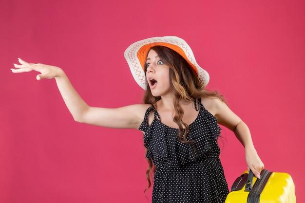 Giovane bella ragazza in abito a pois in cappello estivo che tiene la valigia essendo in ritardo chiedendo di aspettare agitando con la mano in piedi su sfondo rosa