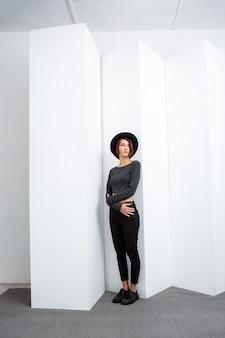 Giovane bella ragazza in cappello nero che posa sopra la parete bianca