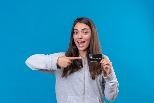 Giovane bella ragazza in felpa con cappuccio grigia che guarda l'obbiettivo con il sorriso sul viso tenendo e puntando la carta di credito in piedi su sfondo blu