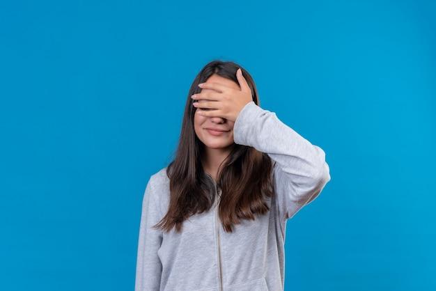 Giovane bella ragazza in felpa con cappuccio grigia con la mano sulla testa in piedi su sfondo blu