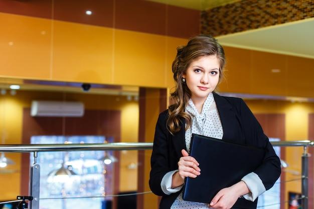 Giovane bella ragazza in piedi in un ufficio e in possesso di un computer portatile