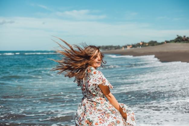Giovane bella ragazza in posa sulla spiaggia, oceano, onde, sole splendente e pelle abbronzata