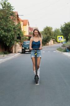 Giovane bella ragazza in sella a uno scooter elettrico in estate sulla strada