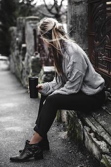 Giovane bella ragazza in un caldo maglione lavorato a maglia e stivali in posa sulla strada, sul ritratto di strada, per chiudere il modello