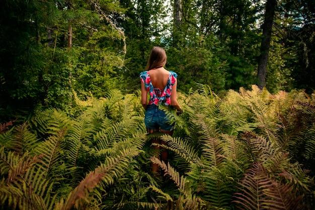Giovane bella ragazza in una felce in una foresta estiva