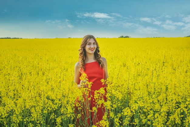 Giovane bella ragazza in una fine rossa del vestito in su nel mezzo del campo giallo con i fiori del ravanello. stagione primaverile