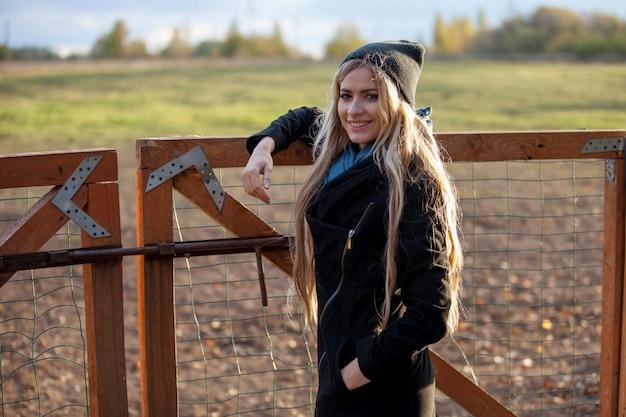 Giovane bella ragazza in una stalla, all'aperto, donna al recinto