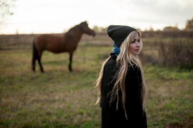 Giovane bella ragazza in una stalla, all'aperto