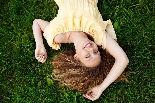 Giovane bella ragazza in vestito giallo che si trova sull'erba.