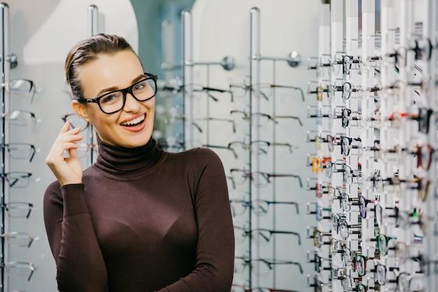 Giovane bella ragazza in vetri vicino allo stand nel negozio di ottica.
