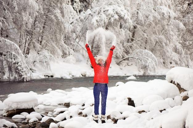 Giovane bella ragazza nella foresta di inverno vicino al fiume