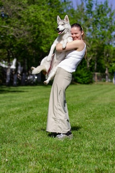 Giovane bella ragazza riccia che gioca con il suo cane con un piatto di frisbee nel parco estivo. cane husky siberiano