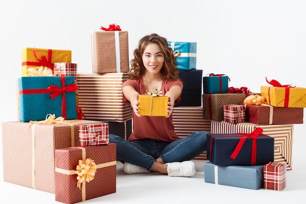 Giovane bella ragazza riccia che si siede sul pavimento fra i contenitori di regalo isolati