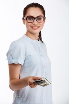 Giovane bella ragazza sicura di affari in vetri che danno soldi sopra la parete bianca