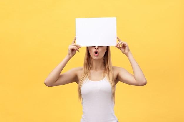Giovane bella ragazza sorridente e in possesso di un foglio di carta bianca