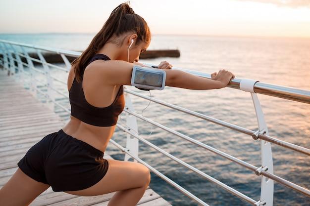 Giovane bella ragazza sportiva che si prepara all'alba sulla spiaggia.