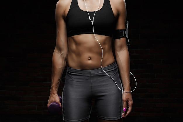 Giovane bella ragazza sportiva che si prepara sopra la fine scura della parete in su.