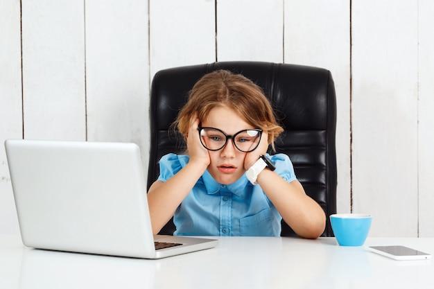 Giovane bella ragazza stanca che si siede al posto di lavoro in ufficio.