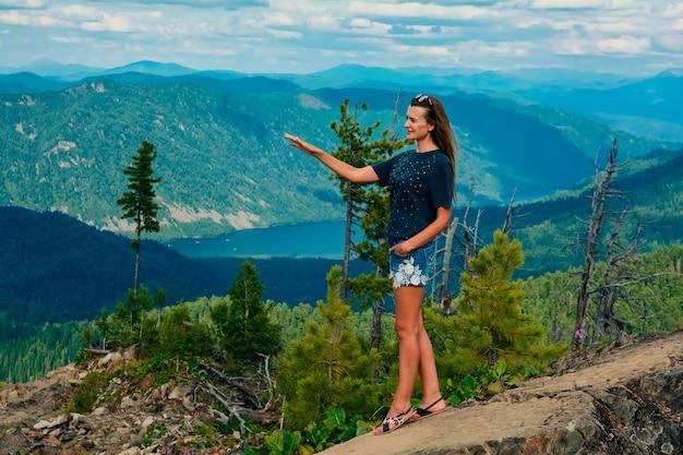 Giovane bella ragazza su un bellissimo paesaggio di montagna in estate