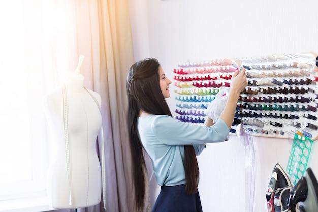 Giovane bella sarta guardando fili per tessuti nel suo posto di lavoro.