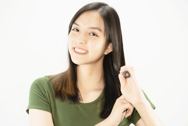 Giovane bella signora felice facendo uso del pettine a diritto i suoi capelli - concetto di cura di capelli di bellezza della donna
