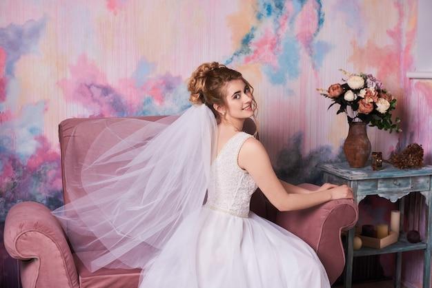 Giovane bella sposa che si prepara per il tiro di foto di nozze