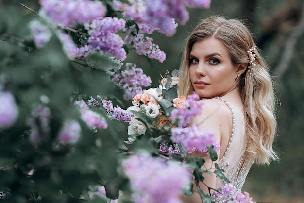 Giovane bella sposa con un mazzo di nozze vicino ai cespugli lilla