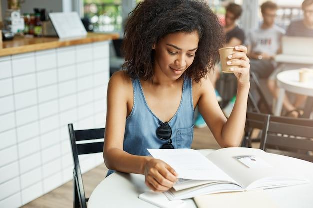 Giovane bella studentessa africana che si siede in caffè che sorride esaminando caffè bevente della rivista. apprendimento ed educazione.