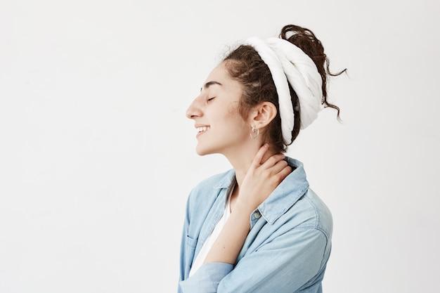Giovane bella studentessa che indossa do-rag sulla testa, con i capelli scuri e ondulati, sorridendo e chiudendo gli occhi con espressione faccia felice, sognando e godendo la vita, in posa contro il muro bianco.