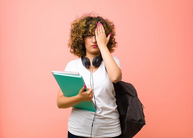 Giovane bella studentessa che sembra assonnata, annoiata e sbadigliata, con un mal di testa e una mano che copre metà del viso contro il muro rosa
