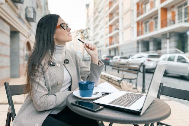 Giovane bella studentessa che si siede in caffè all'aperto con il computer portatile