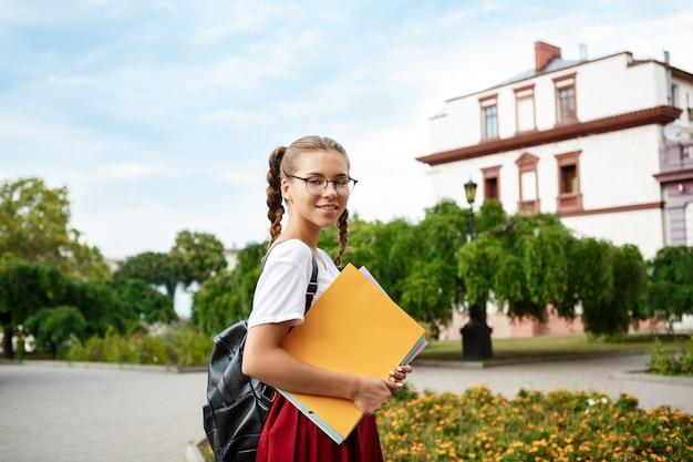 Giovane bella studentessa in bicchieri sorridente, tenendo le cartelle all'aperto.