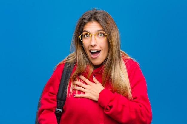 Giovane bella studentessa sentendosi scioccata e sorpresa, sorridendo, prendendosi per mano, felice di essere quella o mostrando gratitudine