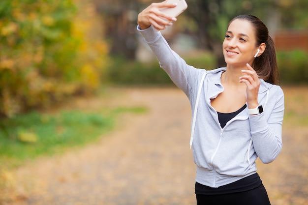 Giovane bellezza con lunghi capelli castani guardando smartphone prendendo foto di se stessa