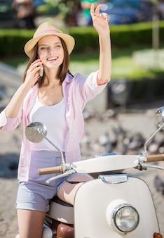 Giovane bellezza in elegante cappello seduto su scooter e sorridente.
