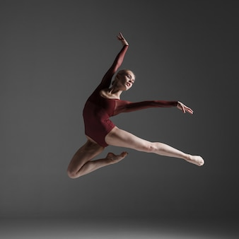 Giovane bello ballerino moderno stile saltando