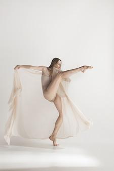 Giovane bello ballerino nel dancing beige del costume da bagno sul gray