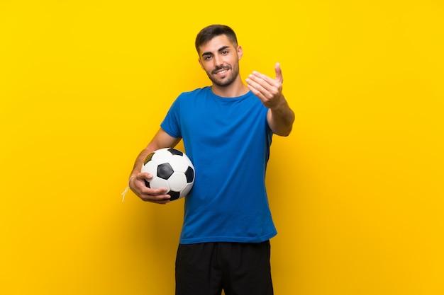 Giovane bello calciatore uomo sopra isolato muro giallo che invita a venire con la mano, felice che tu sia venuto